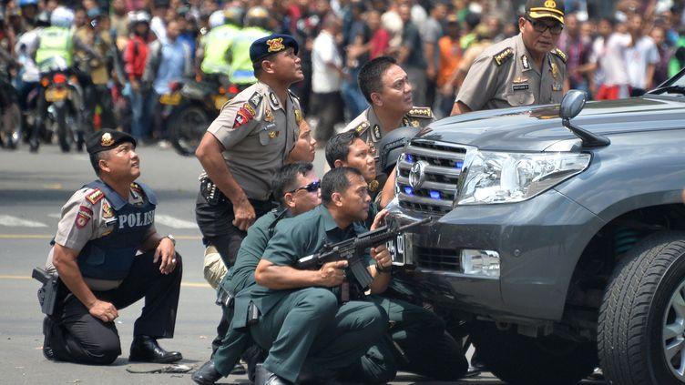 Des policiers indonésiens sont postés derrière un véhicule après une série d'attaques à Jakarta (Indonésie), le 14 janvier 2016. (BAY ISMOYO / AFP)