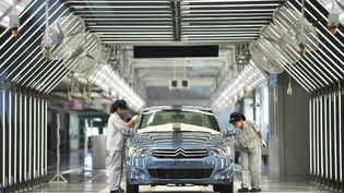 Des employés sur une chaîne de montage d'une usine de PSA Peugeot Citroën, le 2 juillet 2013 à Wuhan (Chine). ( AFP )