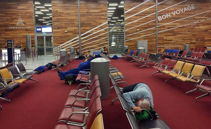 Des personnes dorment à l'aéroport de Roissy-Charles-de-Gaulles alors que les routes sont impraticables en raison de la neige, mardi 7 février 2018. (INGRID BAZINET / AFP)