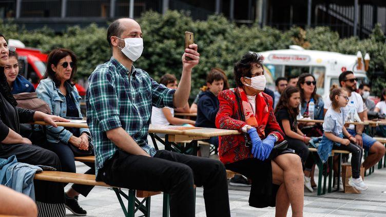 Des spectateurs portent des masques pendant la fête de la Musique, dimanche 21 juin 2020, à l'institut du monde arabe, à Paris. (ABDULMONAM EASSA / AFP)
