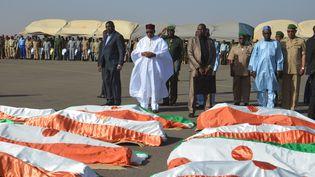 Le président du nigérienMahamadou Issoufou, le 13 décembre 2019, devant les corps des militaires tués dans une attaque contre un camp militaire à Inates (ouest du Niger), trois jours avant. (BOUREIMA HAMA / AFP)