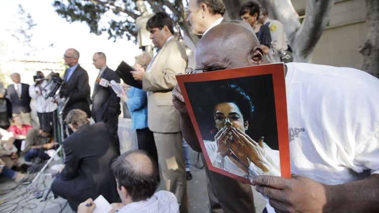 """Un fan de Michael Jackson exhibant une photo du chanteur morten 2009, le 2 octobre 2013, à la sortie du tribunal de Los Angeles (Etats-Unis) où la famille du """"Roi de la pop"""" vient de perdre son procès contre le promoteur de la star. (JAE C. HONG / AP / SIPA)"""