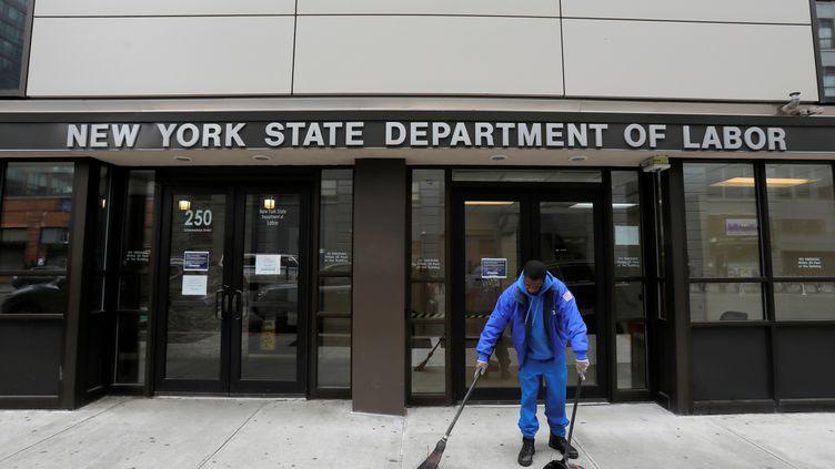 Un homme nettoie l'entrée du département du Travail de New York (Etats-Unis), le 20 mars 2020. (ANDREW KELLY / REUTERS)
