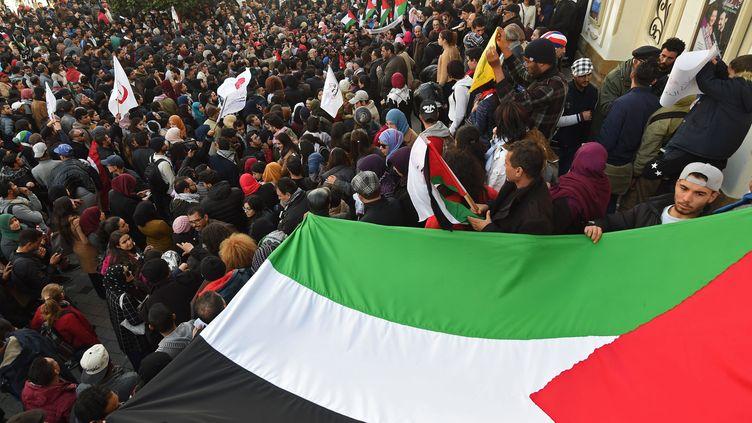 Des Tunisiens brandissent un drapeau palestinien pour protester contre la décision de Donald Trump de reconnaître Jérusalem comme la capitale d'Israël, le 7 décembre 2017 à Tunis (Tunisie). (FETHI BELAID / AFP)