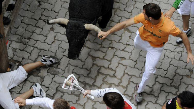 Des hommes courent à côté de taureaux, mercredi 11 juillet, lors desfêtes de la San Fermin, à Pampelune (Espagne). (ANDER GILLENEA / AFP)