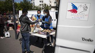 Des bénévoles du Secours populaire distribuant de la nourriture et des produits d'hygiène aux étudiants précaires, le 6 mai 2020 à Saint-Denis en région parisienne. (THOMAS SAMSON / AFP)