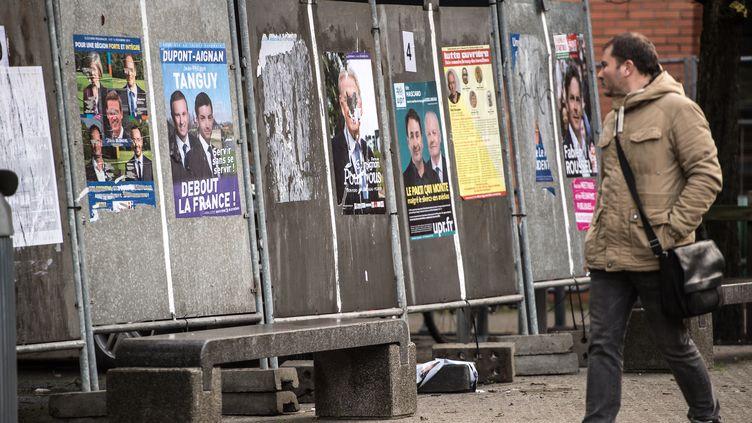 Un homme passe devant des panneaux électoraux avant les élections régionales, le 1er décembre2015, à Lille (Nord). (PHILIPPE HUGUEN / AFP)