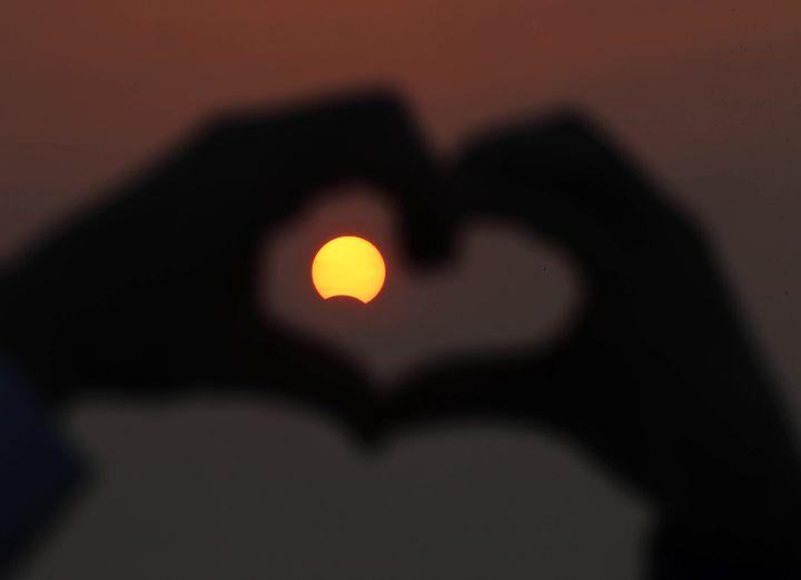 Un homme forme un cœur avec ses doigts autour de l'éclipse solaire, au Koweit, le 3 novembre 2013. (YASSER AL-ZAYYAT / AFP)
