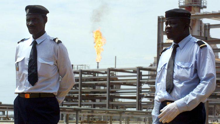 Deux policiers en faction devant le puits de pétrole de Komé,au sud du Tchad. Un pipeline de 1000 km traversant le Cameroun permet au Tchad depuis 2003 d'exporter son pétrole. (DESIREY MINKOH / AFP)