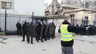 """Un """"gilet jaune"""" fait face à des gendarmes devant l'Assemblée nationale à Paris, le 9 février 2019. (ZAKARIA ABDELKAFI / AFP)"""