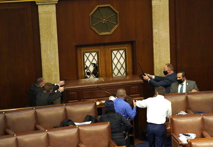 Des officiers de police pointent leurs armes en direction de manifestants qui tentent de pénétrer par la force dans la Chambre des représentants, à Washington, mercredi 6 janvier 2021. (DREW ANGERER / GETTY IMAGES / AFP)