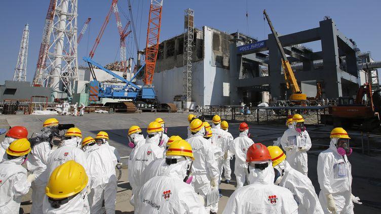 Des employés de la compagnieTepco inspectent le bâtiment du réacteur n°4 de la centrale de Fukushima, le 6 mars 2013. (ISSEI KATO / GETTY IMAGES)