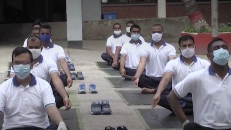 Pour gérer leur stress durant l'épidémie, des policiers du Bangladesh participent à des cours collectifs de yoga. (FRANCEINFO)