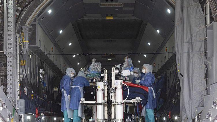 Des soignants vérifient les équipements médicaux installés dans un Airbus A400M avant une évacuation de patients infectés par le nouveau coronavirus sur la base aérienne de Matoury, près de Cayenne, le 28 juin 2020. (JODY AMIET / AFP)
