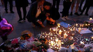 Deux femmes rendent hommage, mardi 23 avril, aux victimes de l'attentat de Manchester (Royaume-Uni). (PETER NICHOLLS / REUTERS)