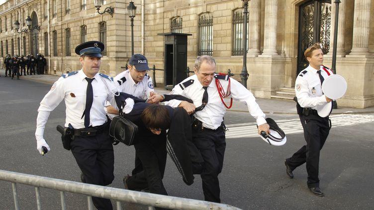 Non loin de l'ambassade américaine, à proximité de l'Elysée, des policiers interpellent un manifestant venu protester le 15 septembre 2012 contre le film islamophobe à l'origine de violences antiaméricaines. (BENOIT TESSIER / REUTERS)
