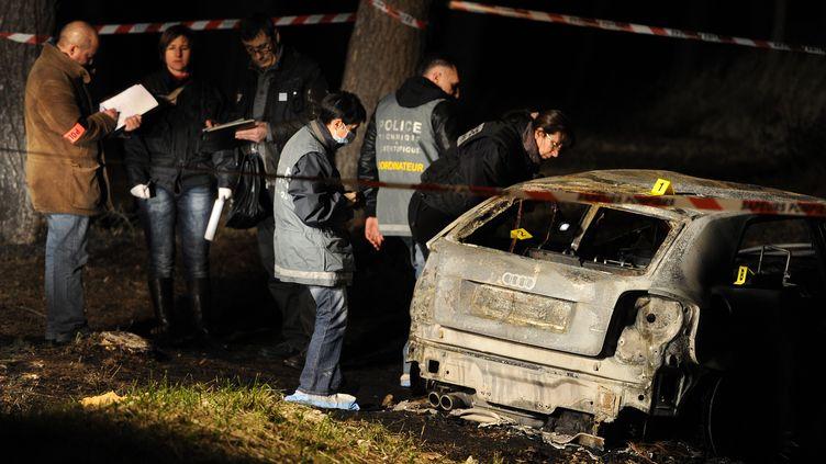 Les enquêteurs procèdent aux premières investigations sur le véhicule calciné dans lequel trois corps ont été retrouvés sur la commune des Pennes-Mirabeau (Bouches-du-Rhône), le 26 décembre 2011. (GERARD JULIEN / AFP)