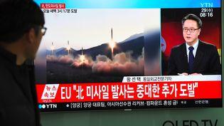 Dans une rue de Séoul, la télévision sud-coréenne annonce le nouveau tir de missile du régime nord-coréen, le 29 novembre 2017. (JUNG YEON-JE / AFP)
