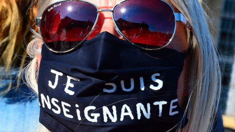 """Une femme porte un masque sur lequel il est écrit """"Je suis enseignante"""", lors d'un rassemblement à Bordeaux en hommage à Samuel Paty, le 18 octobre 2020. (MEHDI FEDOUACH / AFP)"""