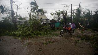 Des habitants circulent à bord d'une moto après le passage du cyclone Matthew à Les Cayes (Haïti), le 4 octobre 2016. (ANDRES MARTINEZ CASARES / REUTERS)