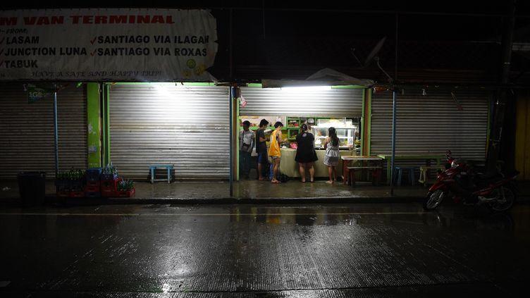 Des haitants deTuguegarao, au nord de Manille (Philippines) achètent de quoi manger dans un restaurant, le 14 septembre 2018, à l'approche du typhon Mangkhut. (TED ALJIBE / AFP)