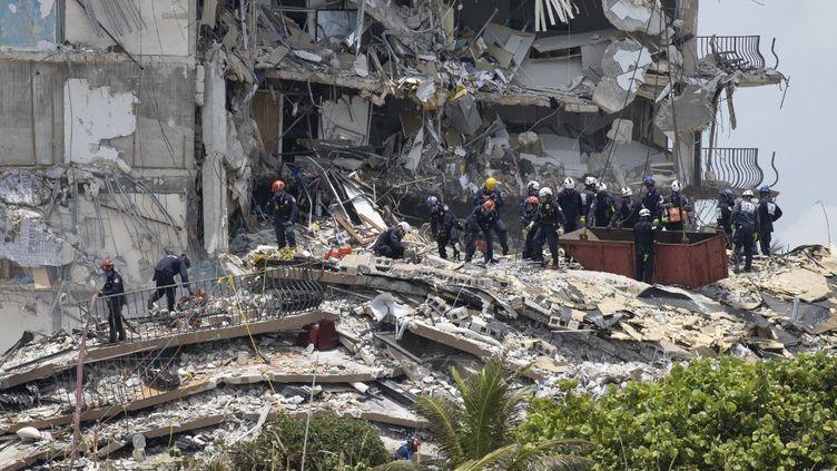 Des membres de l'équipe de sauvetage urbain recherchent d'éventuels survivants dans l'immeuble partiellement effondré, le 26 juin 2021 à Surfside, en Floride (Etats-Unis). (JOE RAEDLE / GETTY IMAGES NORTH AMERICA / AFP)