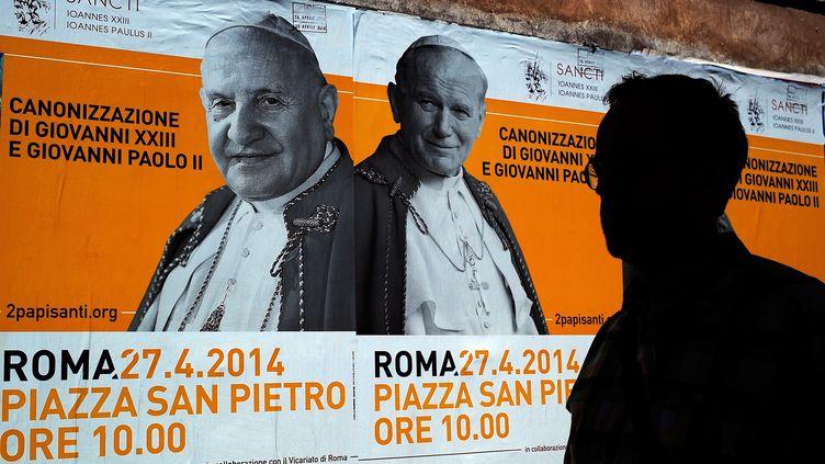 Des affiches annonçant la canonisation de Jean Paul II et Jean XXIII, le 24 avril 2014 à Rome (Italie). (FILIPPO MONTEFORTE / AFP)