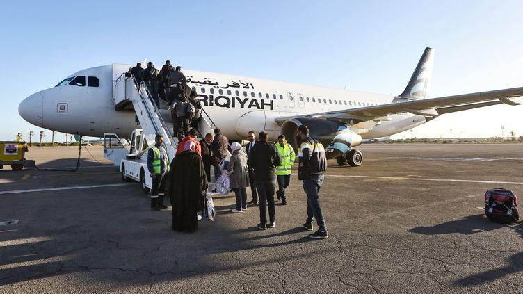 Des passagers embarquent à bord de l'Airbus A320 de la compagnie libyenne Afriqiyah Airways à l'aéroport international de Mitiga, à l'est de la capitale libyenne Tripoli, le 12 décembre 2019. (MAHMUD TURKIA / AFP)