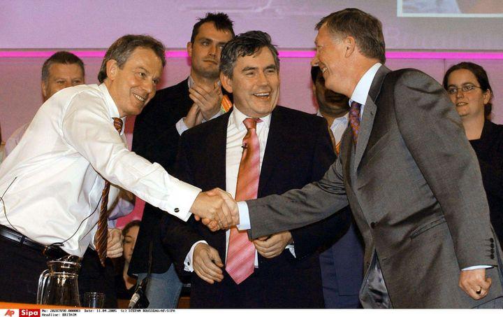 L'entraîneur de Manchester United, Alex Ferguson, serre la main de Tony Blair, premier ministre britannique, sous les yeux de Gordon Brown, alors ministre des Finances, le 11 avril 2005. (STEFAN ROUSSEAU/AP/SIPA / PA)