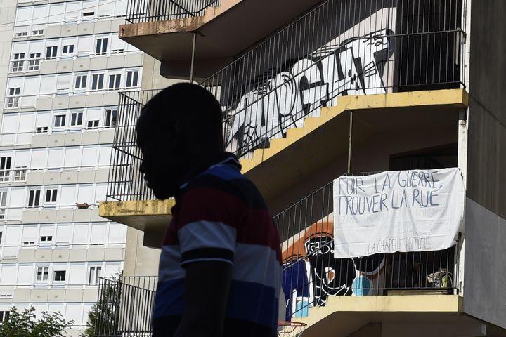 Un migrantdans la cour du lycée désaffecté Jean-Quarré, à Paris, le 2 août 2015. (ALAIN JOCARD / AFP)