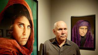 Steve McCurry posant à côté de son célèbre portrait de la jeune afghane Sharbat Gula.  (Ulrich Perrey/DPA/AFP)