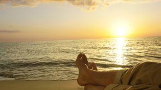 Allongé sur une plage, un homme regarde un coucher de soleil sur la mer. Image d'illustration. (BERNARD FOUBERT / PHOTONONSTOP / AFP)