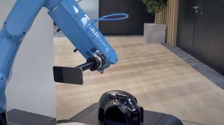 Un bras robotisé simule l'utilisation d'un smartphoneprès de la tête au laboratoire de la société Art-Fi. (ART-FI)