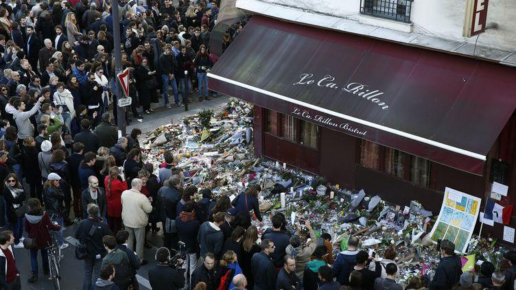 Des dizaines de Parisiens se recueillent devant le bar Le Carillon, le 15 novembre 2015, dans le 11e arrondissement de la capitale. (BENOIT TESSIER / REUTERS)