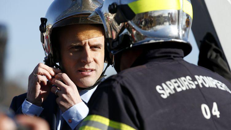 Emmanuel Macron enfile un casque de pompier, le 18 février 2017 à Manosque (Alpes-de-Haute-Provence). (SEBASTIEN NOGIER / EPA)