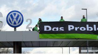"""Des militants de Greenpeace forment """"CO2"""" avec le logo VW et une bannière qui dit """"le problème"""" au dessus de la porte de l'usine Volkswagen à Wolfsburg (Alllemagne), le lundi 9 novembre 2015. (PETER STEFFEN / AP / SIPA)"""