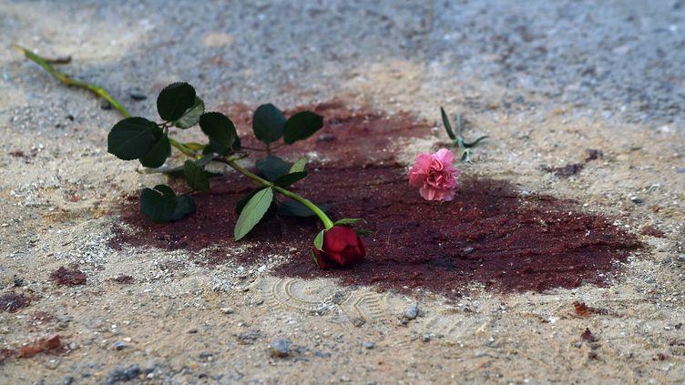 Des fleurs déposées dans une flaque de sang devant le musée du Bardo, le 19 mars 2015,à Tunis (Tunisie), après l'attaque terroriste qui a fait 21 morts. (FADEL SENNA / AFP)
