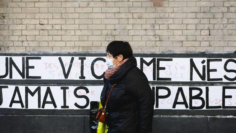 Une femme passe devant un mur sur lequel le collectif Collages féministes ont collé un slogan, à Paris, le 4 novembre 2020. (JEANNE FOURNEAU / HANS LUCAS / AFP)