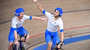 Simone Consonni et FilippoGanna après la victoire de l'Italie lors de la poursuite par équipes, le 4 août aux Jeux olympiques de Tokyo. (GREG BAKER / AFP)
