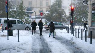Des habitants de Valence (Drôme) marchent dans la neige, le 14 novembre 2019. (NICOLAS GUYONNET / HANS LUCAS / AFP)