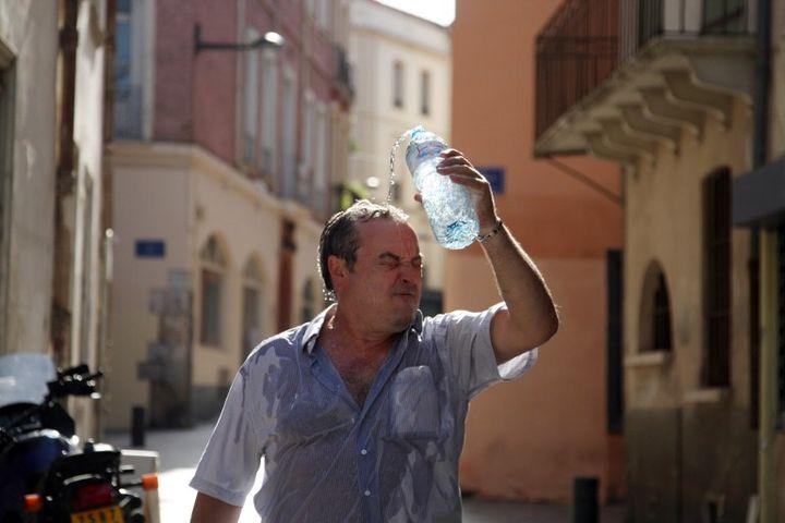 Un homme se rafraîchit à Perpignan (Pyrénées-Orientales), le 17 août 2012. (RAYMOND ROIG / AFP)