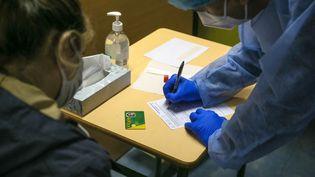 Un soignant note les informations médicales d'une patiente avant un test de dépistage du Covid-19, à Valence (Drôme), le 18 décembre 2020. (NICOLAS GUYONNET / AFP)
