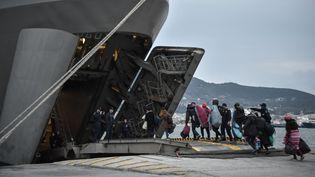 Un groupe de réfugiés entre dans le navire de guerre affrété par la marine grecque dans la port de Mytilène, sur l'île de Lesbos. (LOUISA GOULIAMAKI / AFP)