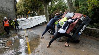 Des habitants de Villegailhenc (Aude) retournent une voiture endommagée par les inondations, le 15 octobre 2018. (ERIC CABANIS / AFP)