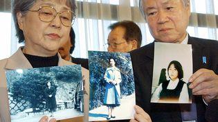 Les parents de Megumi Yokota montrent des photos de la jeune fille enlevée par la Corée du Nord, le 16 novembre 2004 lors d'une conférence de presse à Tokyo (Japon). (AFP / JIJI PRESS)