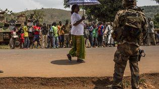 Un soldat de Sangaris est observé par la population à Bangui. Les troupes françaises viennent de trouver une cache d'arme, ce 11 février 2014. (LAURENCE GEAI / SIPA)