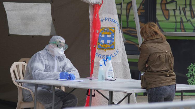 Une tente de dépistage à la Timone, où un marin-pompier accueille une habitante, le 2 avril 2020. (GIACOMO ITALIANO / MAXPPP)