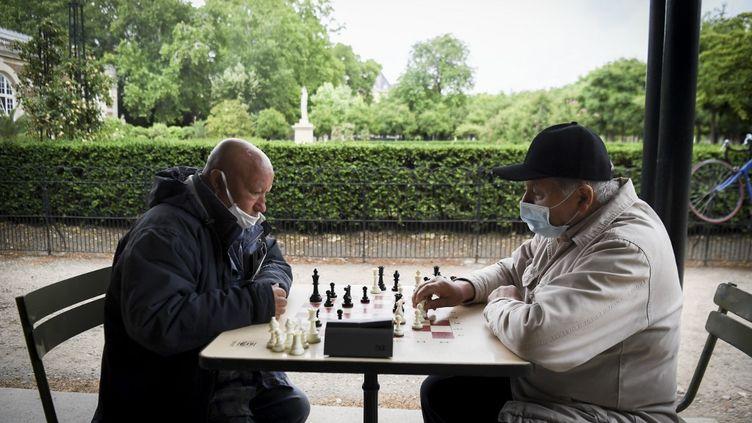 Deux hommes jouent aux échecs au jardin du Luxembourg, le 4 juin 2020 à Paris. (ALAIN JOCARD / AFP)