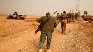 Des combattants kurdes s'approchent d'un véhicules explosé, le 24 octobre 2016, sur le front de Mossoul en Irak. (AHMED JADALLAH / REUTERS)
