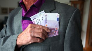 """Des billets de 500 euros dans la poche d'un retraité. Photo d'illustration. Le gouvernement va réguler les """"retraites chapeaux"""" des dirigeants. (EYESWIDEOPEN / GETTY IMAGES EUROPE)"""